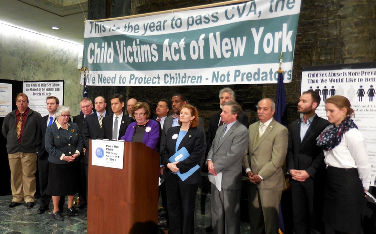 """People standing at a podium with a banner that reads, """"Child Victims Act of New York."""""""
