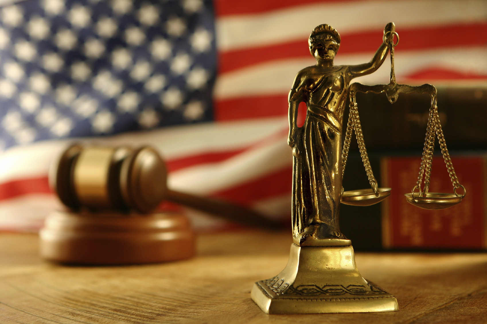 Scales of Justice statue in front of a American flag, a judges gavel, and books blurred in the background.
