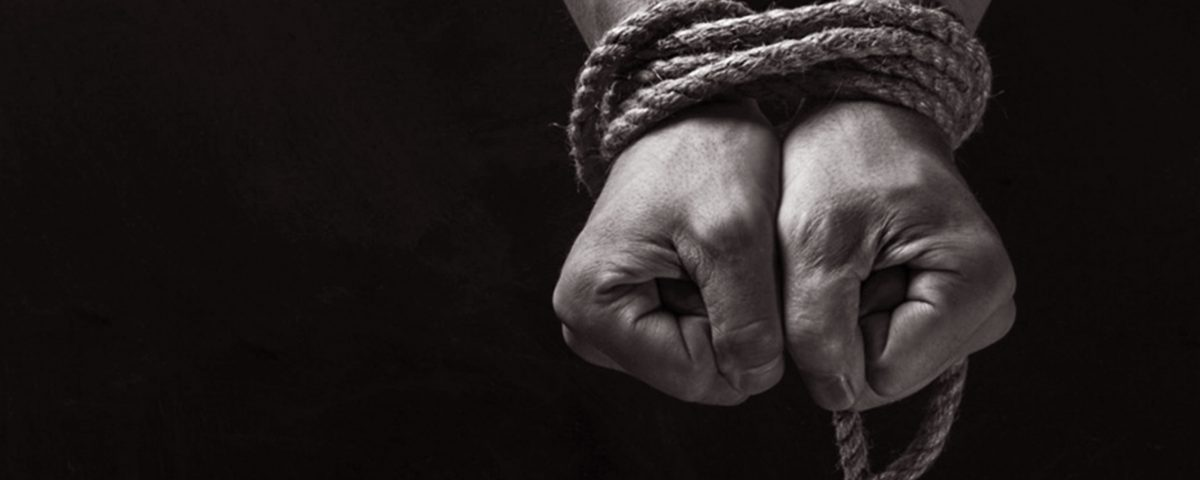 A black and white photograph of a persons hands bound in rope.