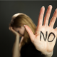 """A photograph of a woman blurred holding her head in her hand, while her other hand is raised up with marker written on it stating, """"NO."""""""