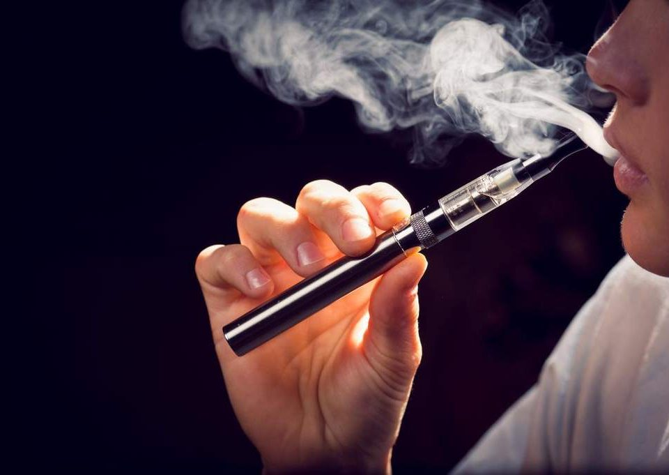 A person vaping a e-cigarette with a cloud of vapor surrounding them.
