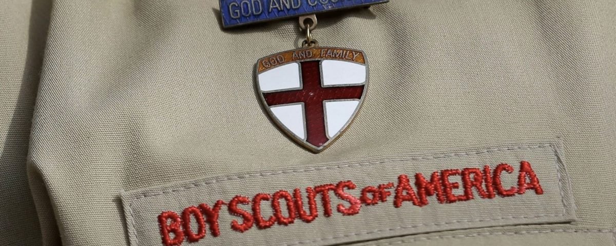 "Boy Scouts of America uniform zoomed in on the insignia and a metal that reads ""God and Country, God and Family."""