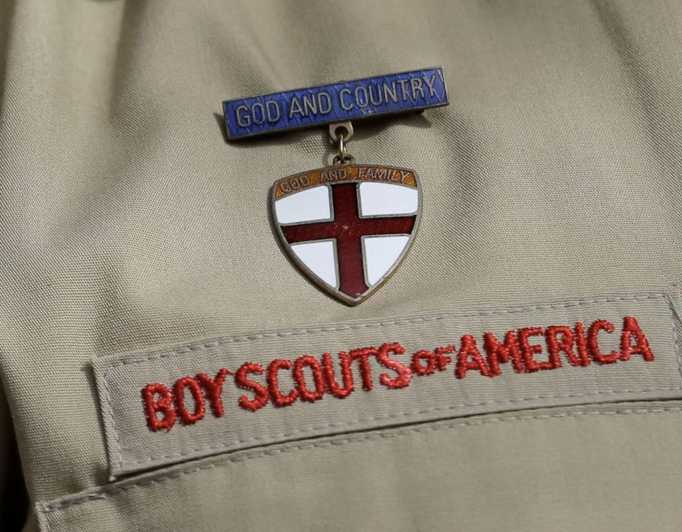 """Boy Scouts of America uniform zoomed in on the insignia and a metal that reads """"God and Country, God and Family."""""""