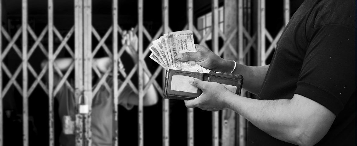 A person behind bars blurring off in the background with a person on the other side of the bars holding a wallet full of money.
