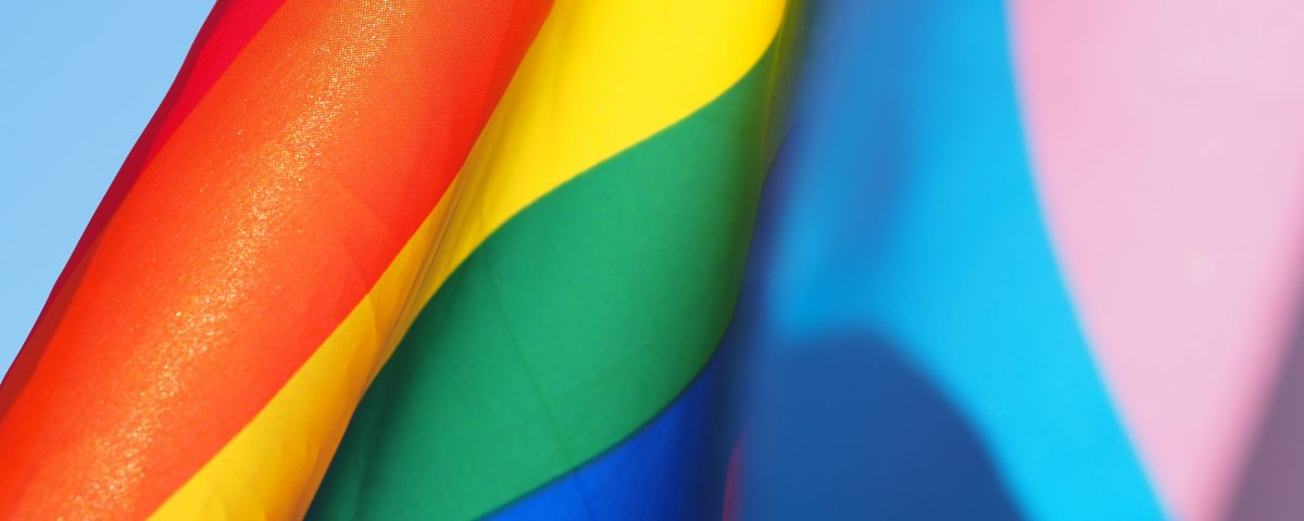 LGBTQ Rainbow Flag blowing in the breeze over a clear blue sky.