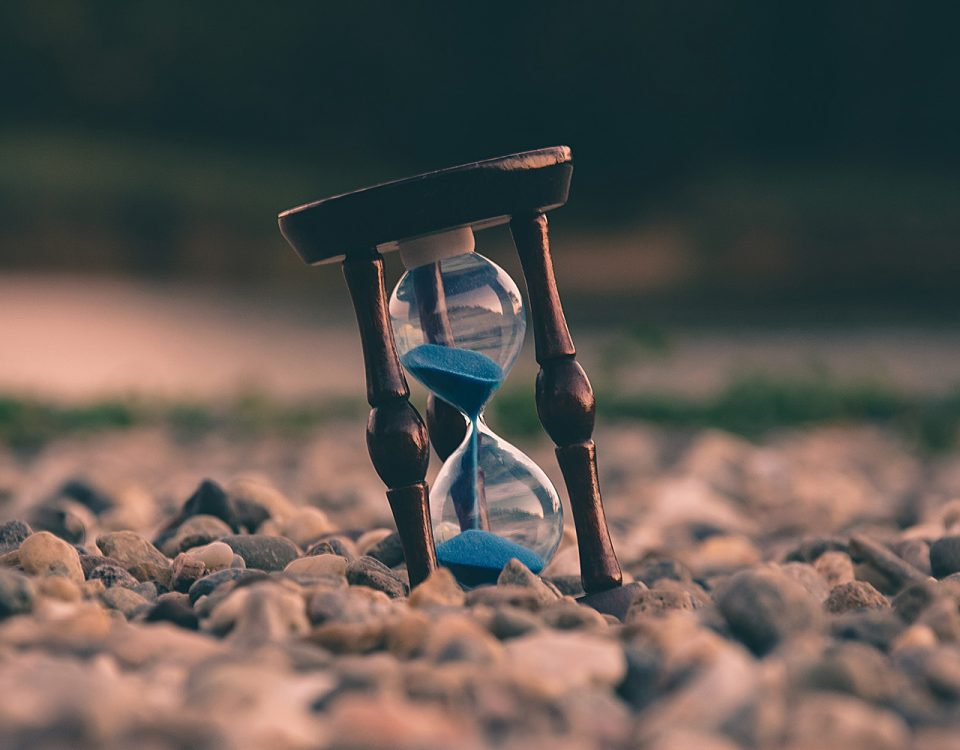 Hourglass with blue sand sitting on a rocky landscape.