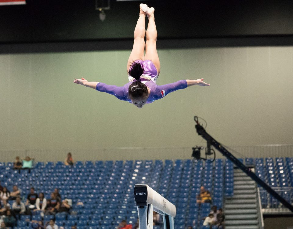 A young woman gymnast is flying through the air doing a gymnastic stunt.