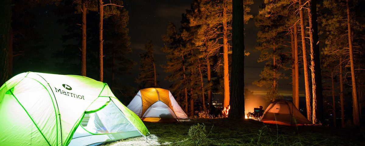 Tents lit up in a dark campsite with a fire and people around the fire in the distance.