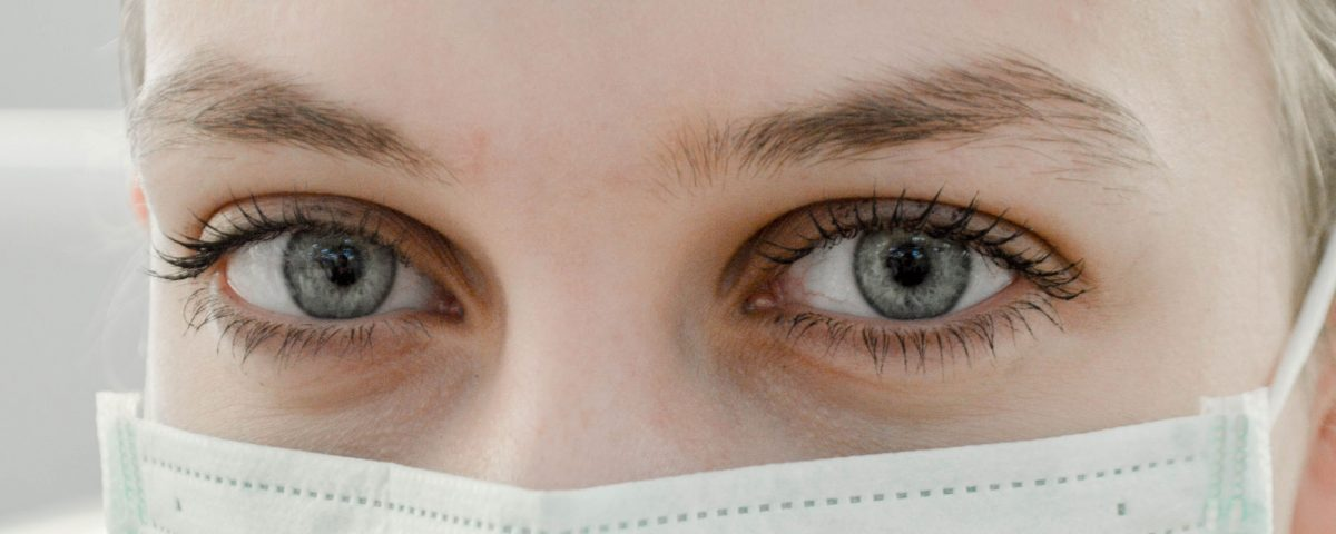 A close up shot of a persons eyes, and a medical mask over their nose and mouth.