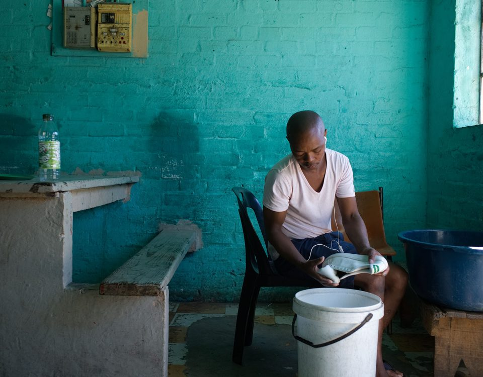 A person in a brick room that is washing shoes over a bucket. The person is sitting with headphones in their ears.