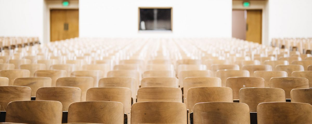 An empty room full of rows of chairs with two exit doors blurred out in the background.