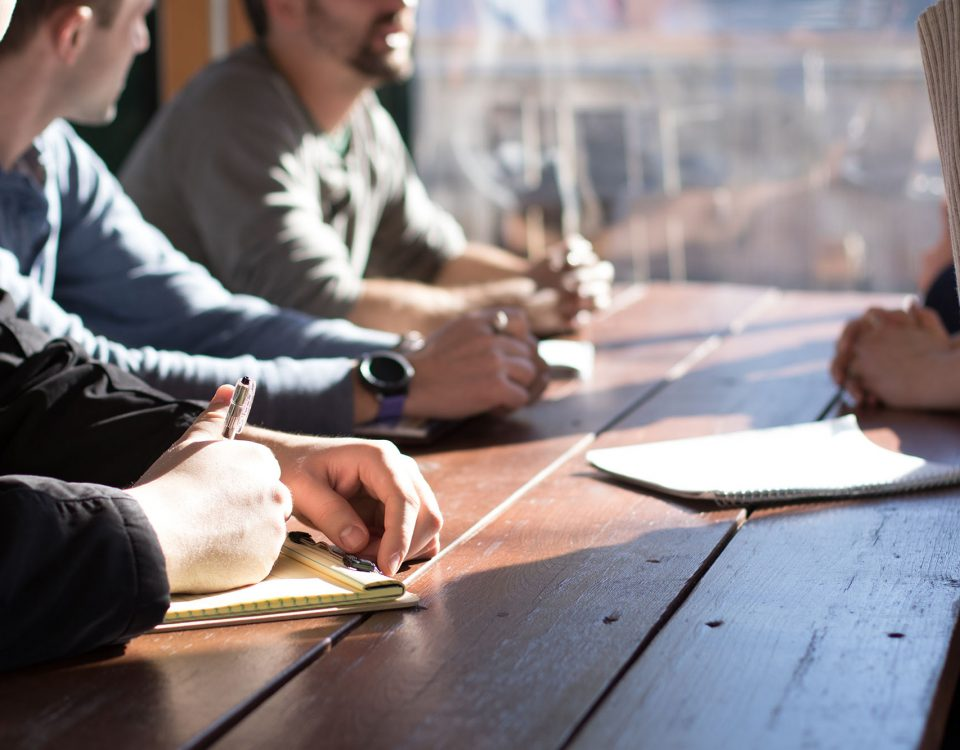 A group of people at a wooden table with paperwork, pens, and discussing legal agreements.