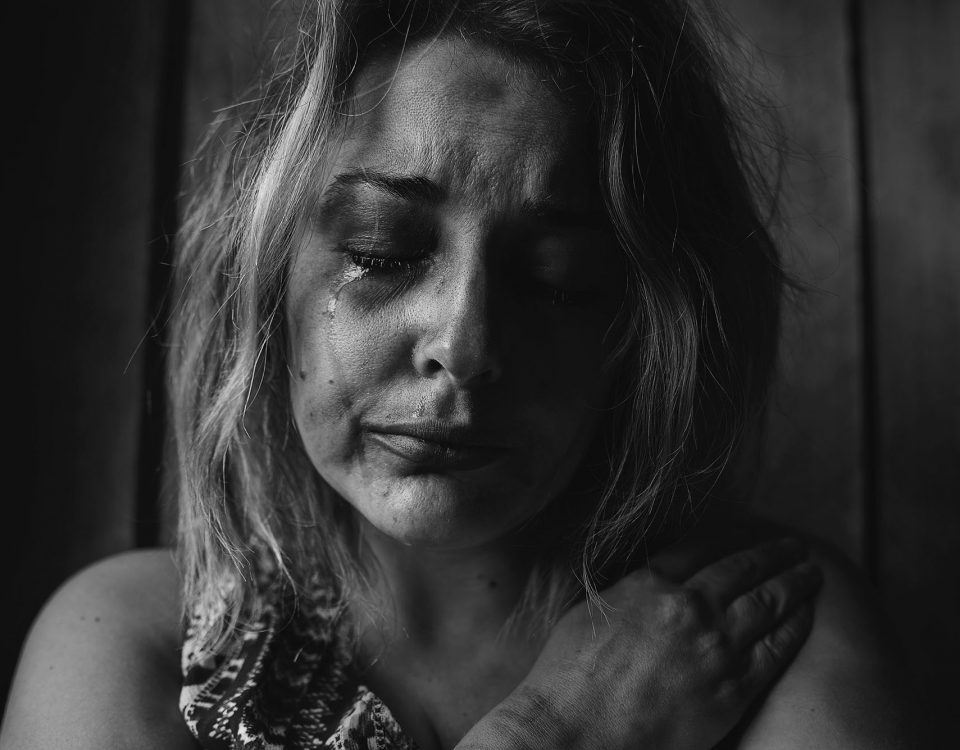 A black and white photograph of a woman crying holding her arm over her chest in a protective fashion.