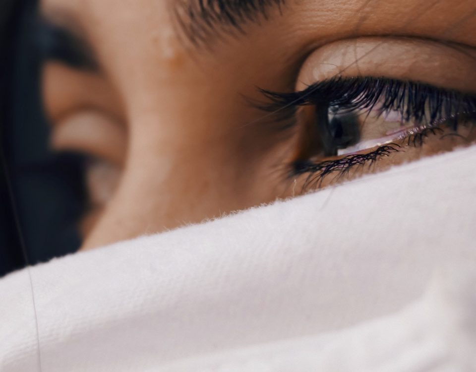 A close up of a persons eyes filled with tears, their face is covered underneath their eyes by a white cloth.