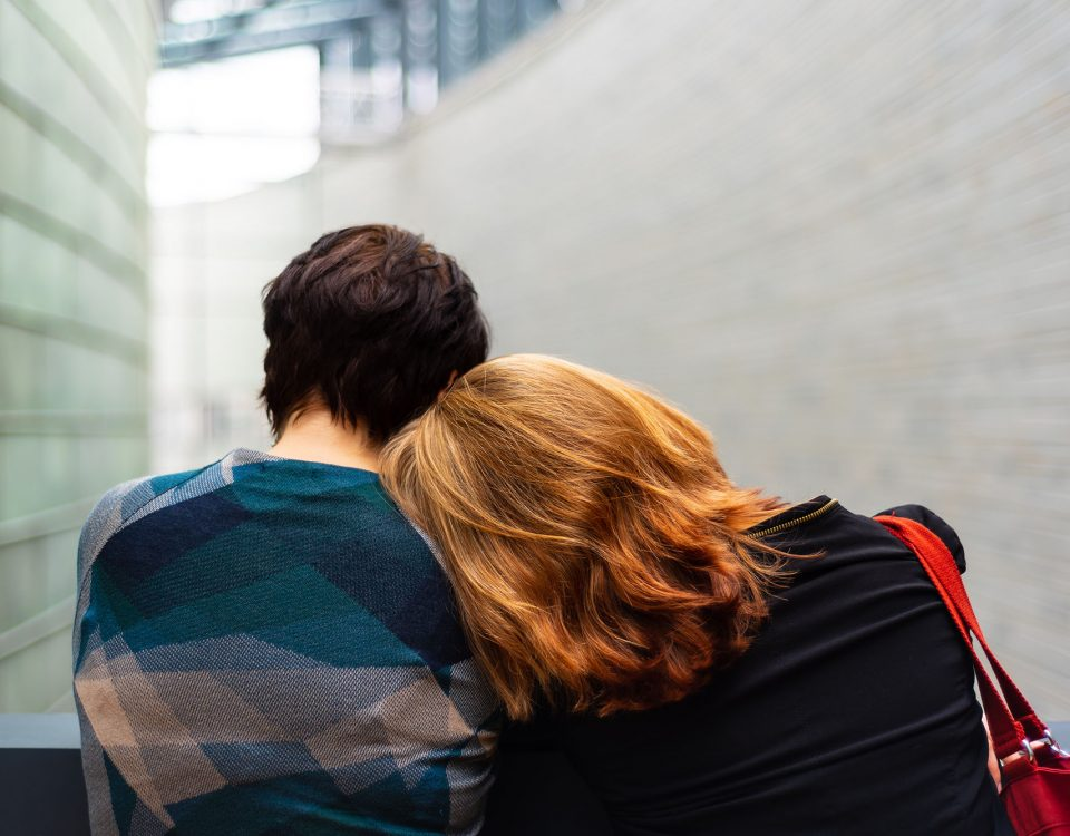 Two people facing away from the camera, the person on the right is laying their head on the person on the lefts shoulder.