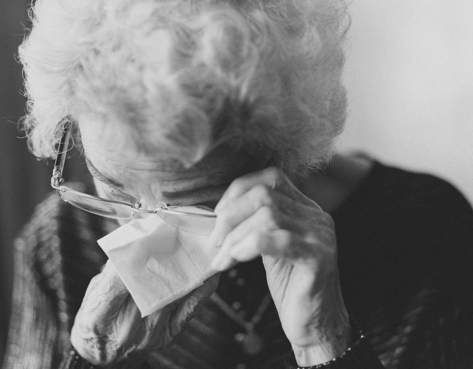 An elderly woman wiping away tears under her glasses, the image is in black and white and it seems that she is deeply sad.