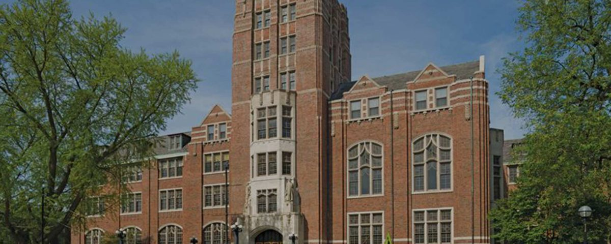 Photograph of a large brick building, Michigan Union, with ornate window panels, trees, and a blue sky in the background.