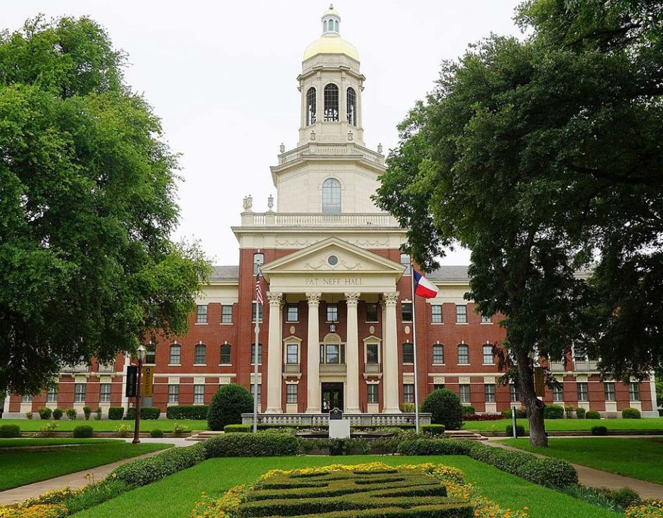 A large lawn leading up to a brick Baylor University building. There is a large tree to the left and to the right of the building. The facade of the building has four large ivory colored columns, with an ornate bell tower on top.