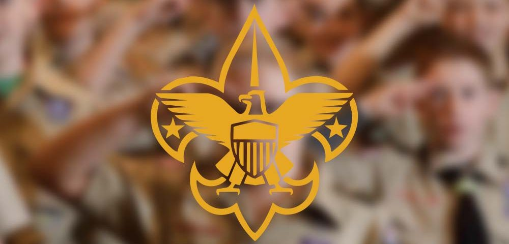 The Boy Scout logo over a blurred out photograph of Boy Scouts saluting in the background.