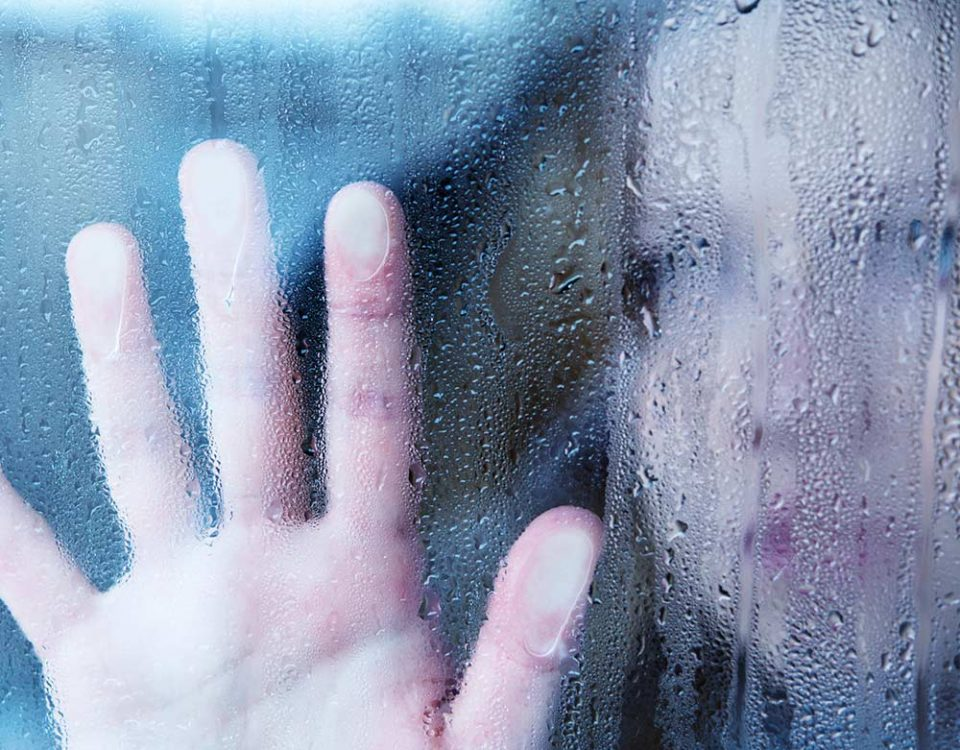 A person places their hand upon a glass window, the rain and condensation blurs the person out of view, but they appear to be sad or deep in thought.