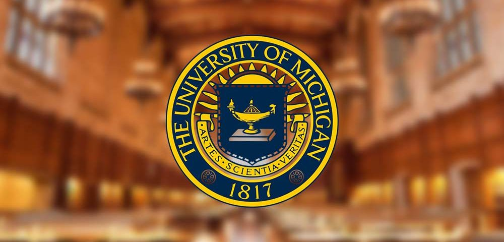 A logo for the University of Michigan. The logo is gold and royal blue, with a depiction of a lamp in the center of the logo. The logo is overlaying a photograph of a blurry room with chairs and lighting, the perspective is guiding the viewer to the end of the room.