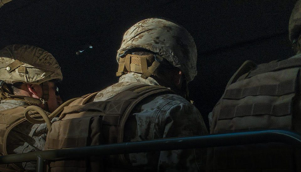 American soldiers are riding in a convoy truck, the back of them is facing the camera, so one can see men in uniform looking forward facing away from the camera. The soldiers are wearing desert camouflage which looks like a pattern across their whole body. We see their helmets and jackets, as well backpacks on their backs.